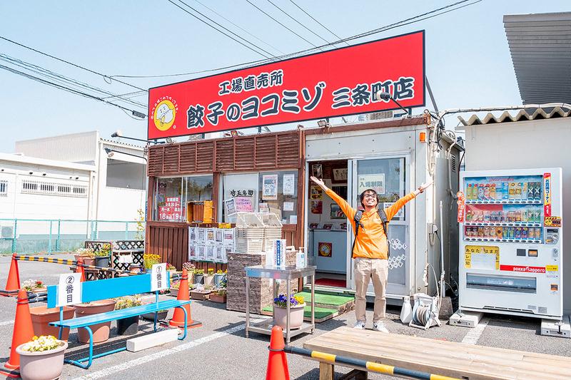 餃子のヨコミゾの前に立つ地主さんの写真