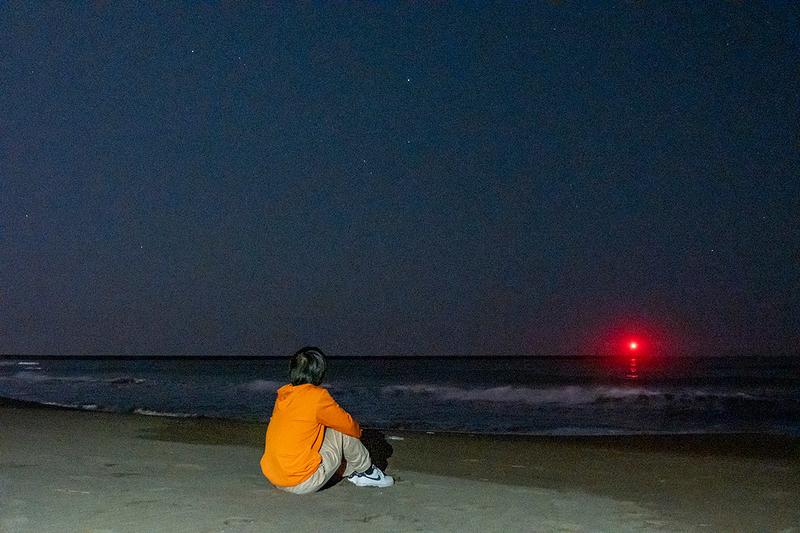 空を眺めている地主さんの写真