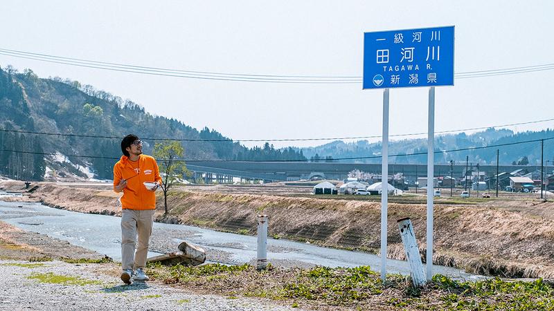 田川と書かれた看板を見る地主さんの写真