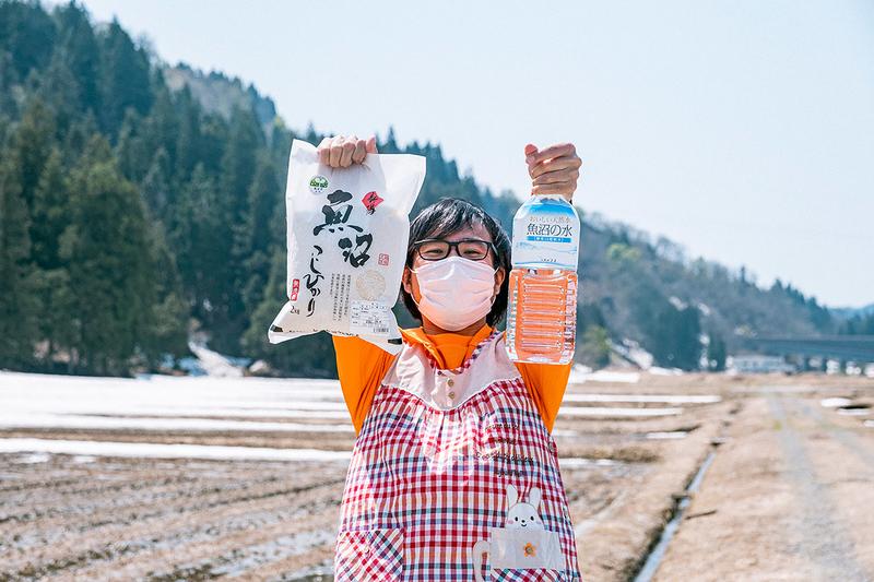 水と米を持つ地主さんの写真
