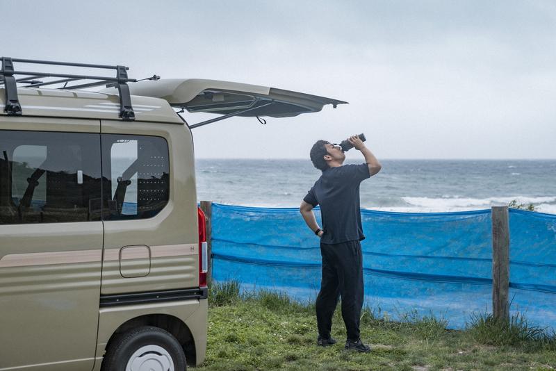 海を眺めながらプロテインを飲む写真