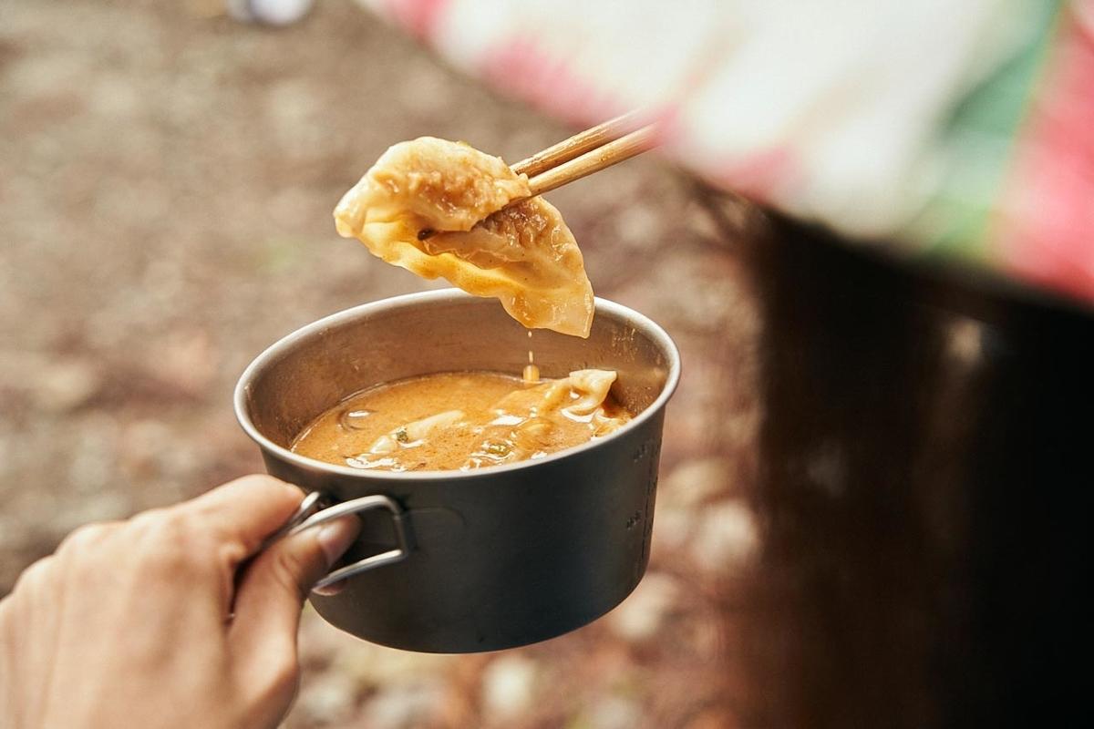 餃子坦坦スープの餃子を箸で持ち上げるともさん