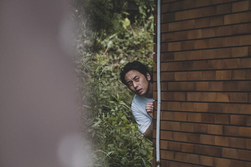 建物に隠れ様子をうかがう受刑者役の大川さん