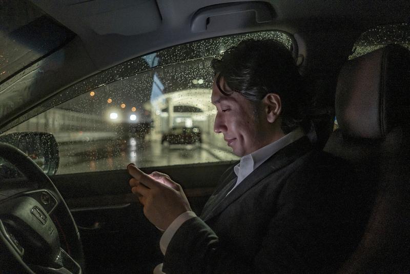 仕事帰り、車内でソーシャルゲームをプレイするサラリーマン