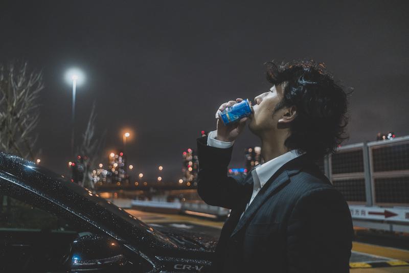 夜景を眺めながら缶コーヒーを飲む男性