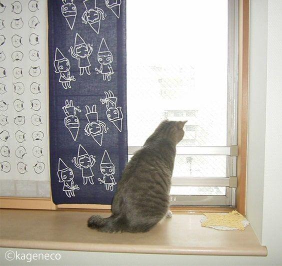 下へと落ちる雪を窓から眺める猫