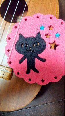 ウクレレに黒猫のコースターを挟んだ写真