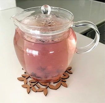 ハーブ茶葉を入れたガラスポットに熱湯を注ぐ