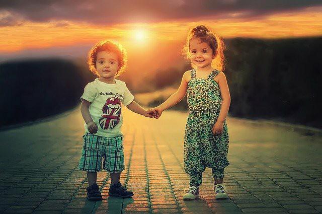 夕日を背景に、男の子と女の子が手をつないでいる。