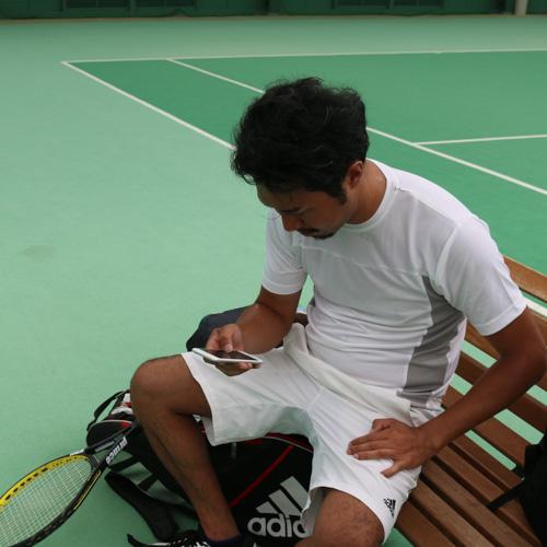 アプリでスマートテニスセンサーのデータをチェックする加藤さん