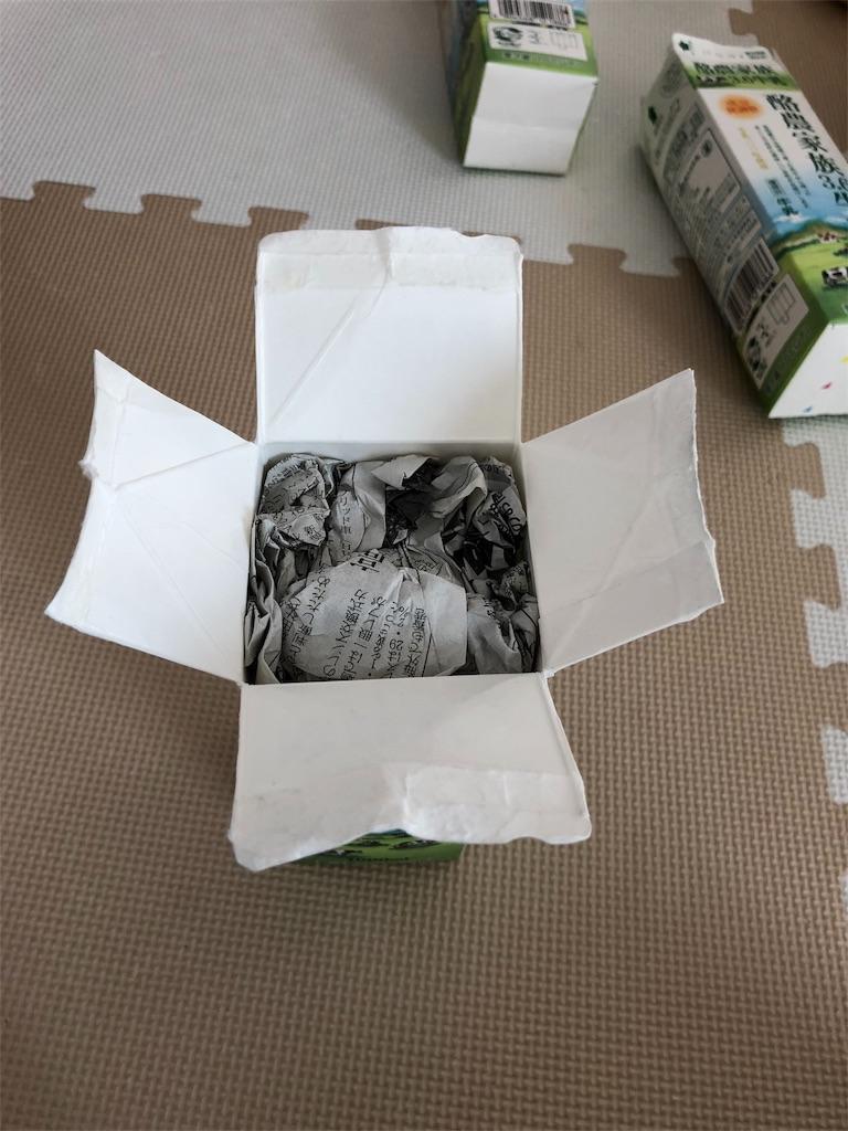 牛乳パック椅子を作るため、新聞紙を詰めた牛乳パックの上部を切り開く