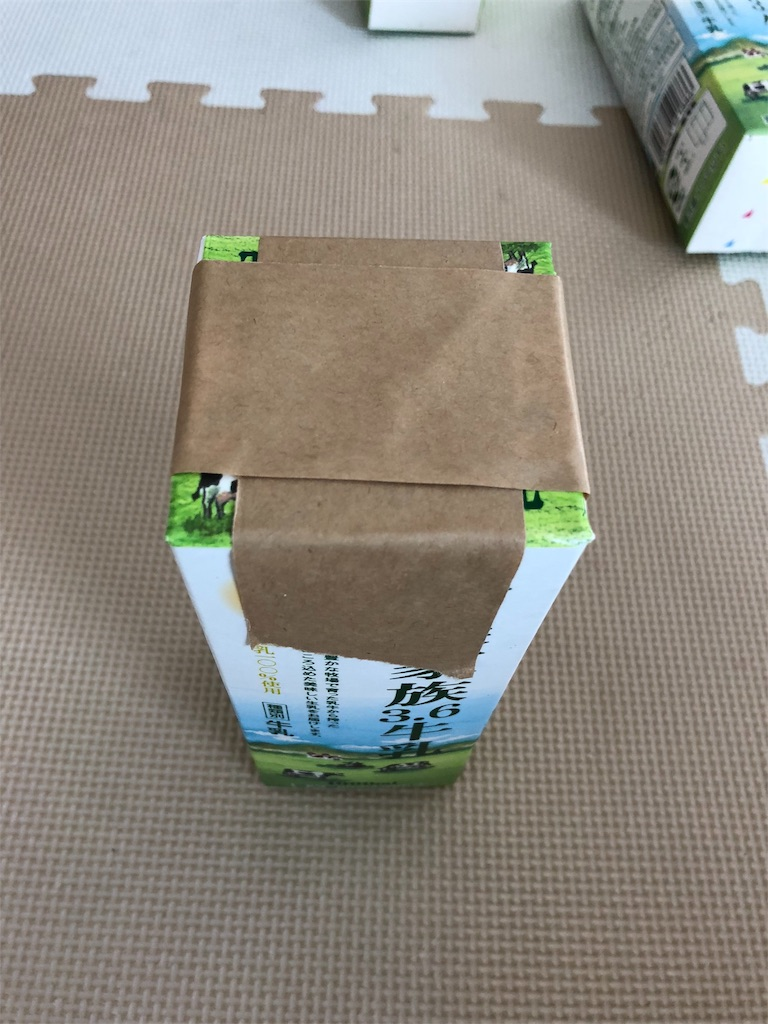 牛乳パック椅子を作るため、新聞紙を詰めた牛乳パックの口をガムテープでとめる