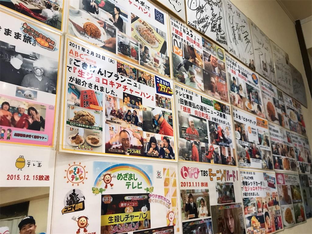 壁一面に有名人の写真やサインが貼られている様子の写真