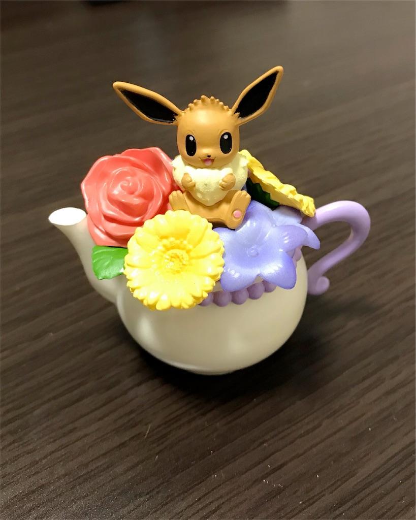 ティーポットの上に咲く花の上にイーブイが乗っているフィギュアの写真