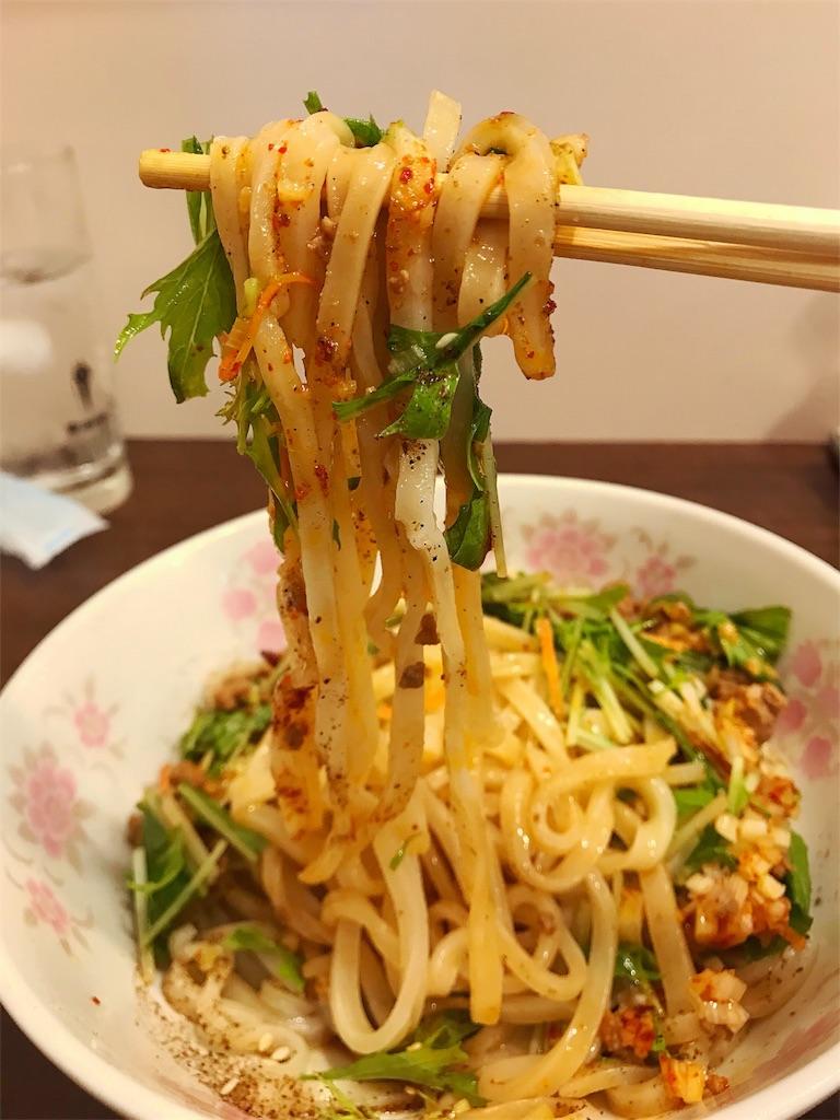 油そばの麺を箸で持ち上げている写真