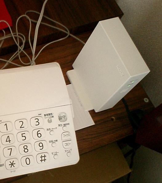 電話機のかたわらに置いてある、ホームプラス電話専用アダプタ