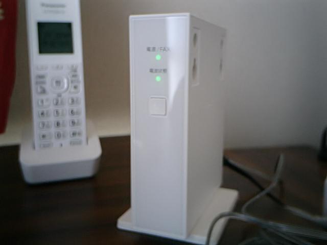 正面から見たホームプラス電話専用アダプタ。アダプタそのものの電源は電話機とは別に壁付コンセントから取る必要があります。停電時など単3乾電池4本を入れても受発信は可能。