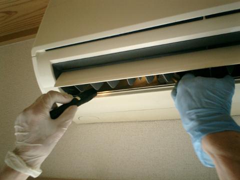 送風ファンの奥、室内機背面側のカビ汚れの拭き取り作業。