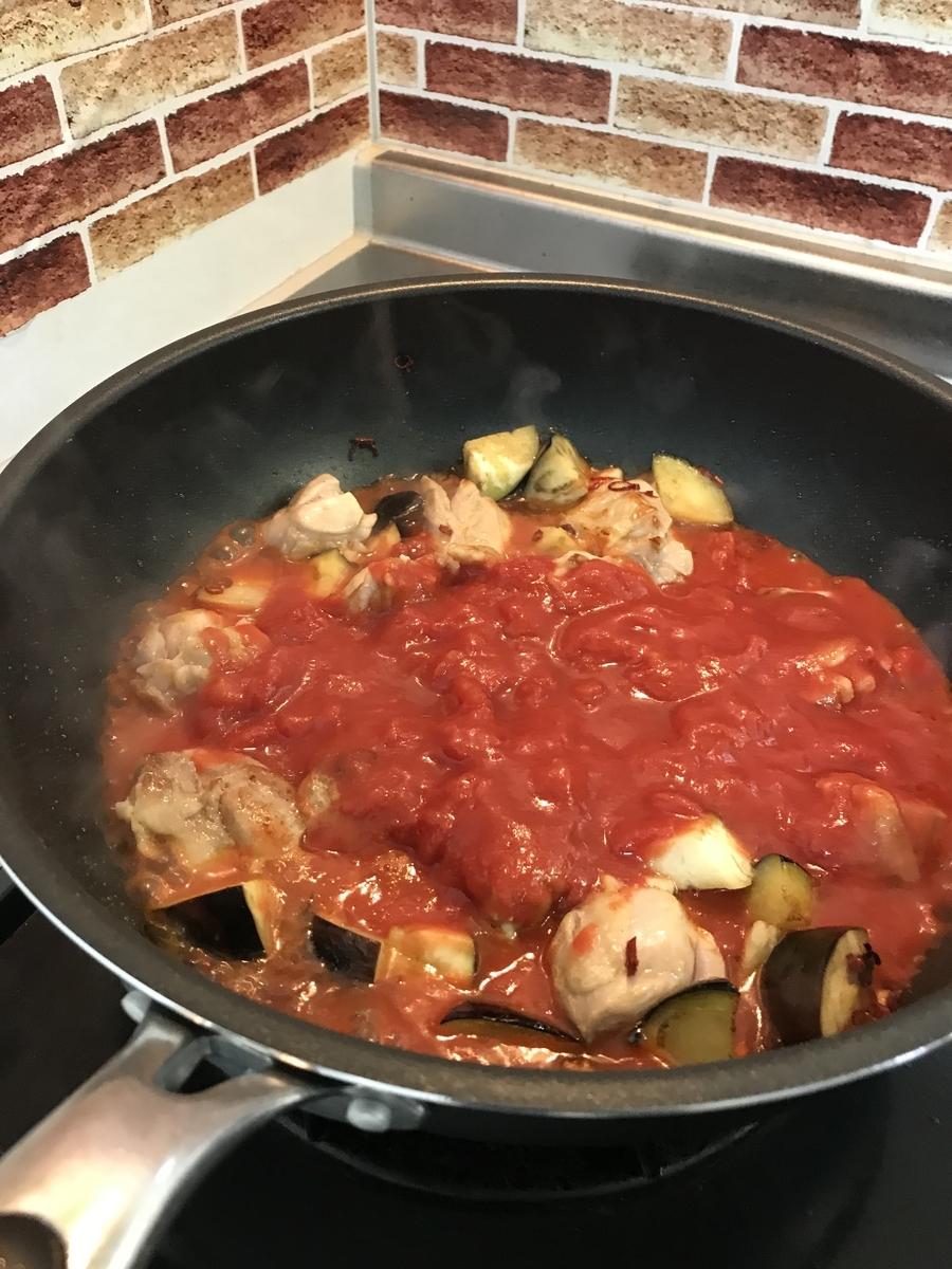 茄子と鶏肉にある程度火が通ったらトマト缶を加えて熱します