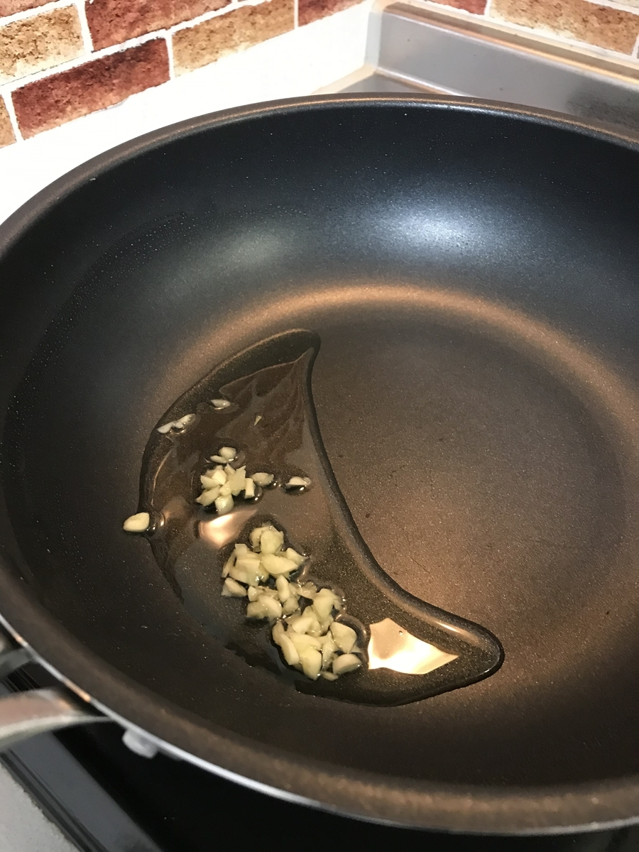 フライパンに刻んだニンニクとオリーブオイルを弱火でゆっくり熱します