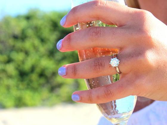 ソフトドリンクを持った女性の左薬指にダイヤのリングをしている写真