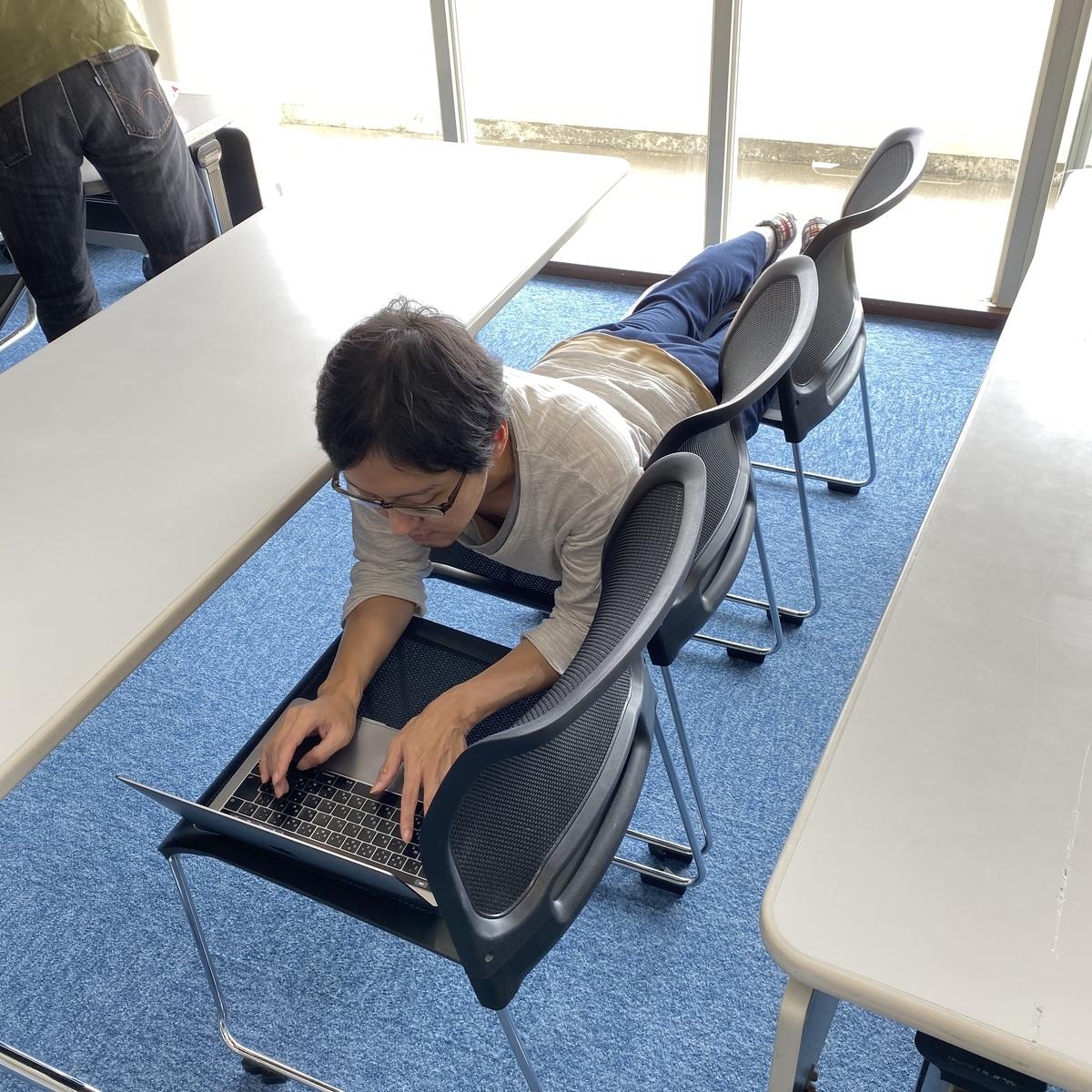 椅子をつなげて寝ながら開発をする人