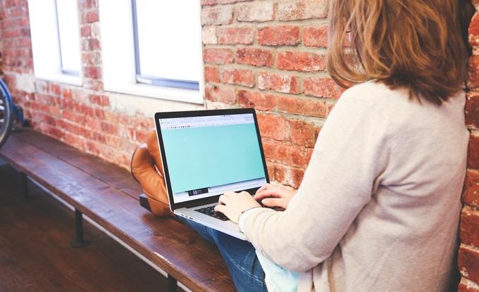 壁際に座ってパソコンを使っている女の子