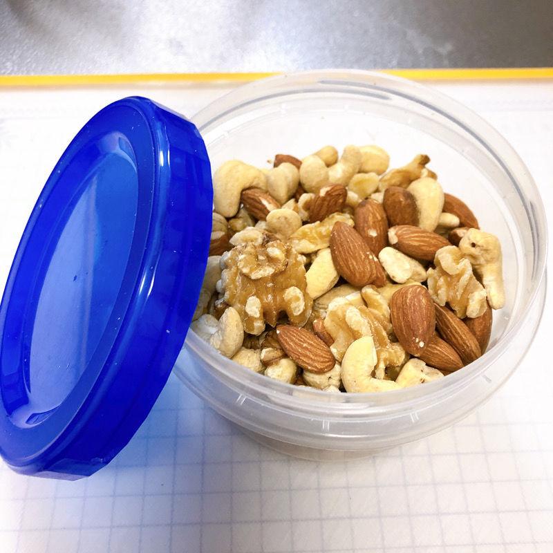 丸いプラスチック製の容器にアーモンド、カシューナッツ、くるみが入っている。