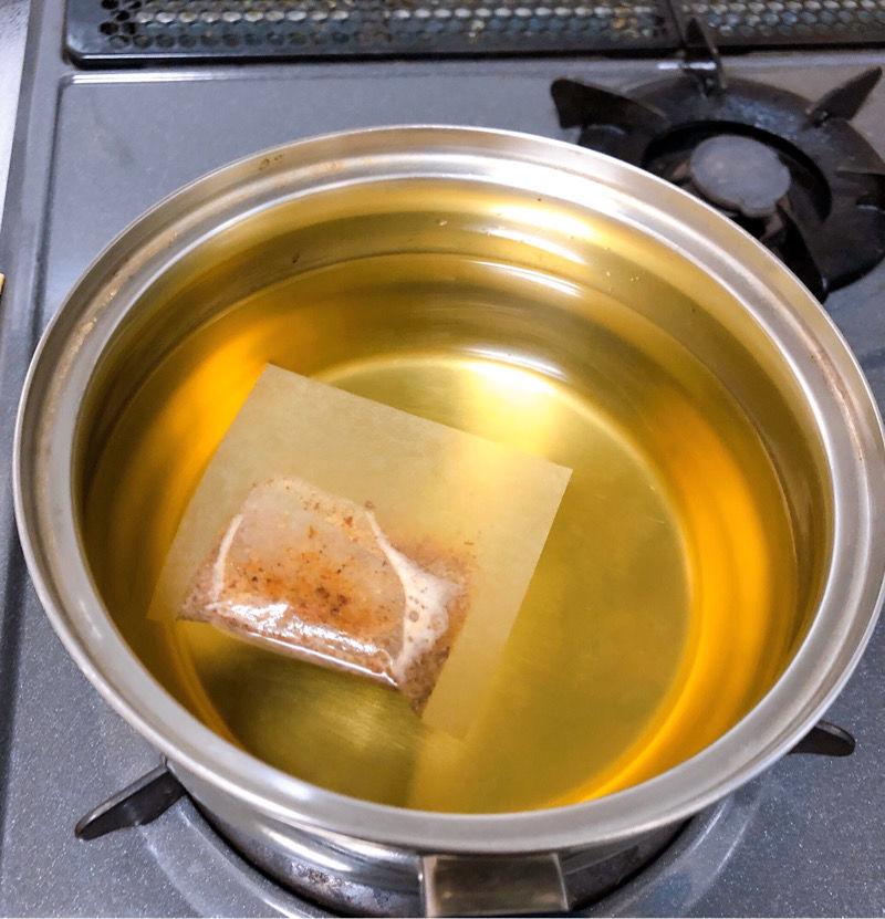 コンロの上に置かれたステンレスの鍋に金色のきれいなだし汁が入っています
