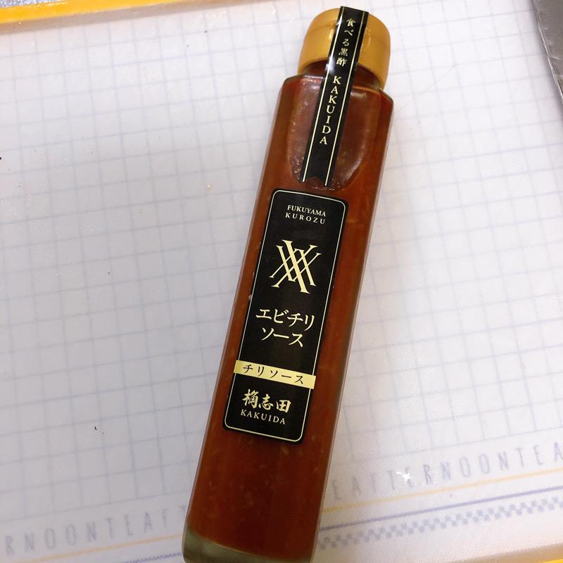 白地のまな板の上に細長い瓶に入ったエビチリソース。ラベルには「食べる黒酢KAKUIDA エビチリソース」という黒字に金文字のラベルが貼ってある