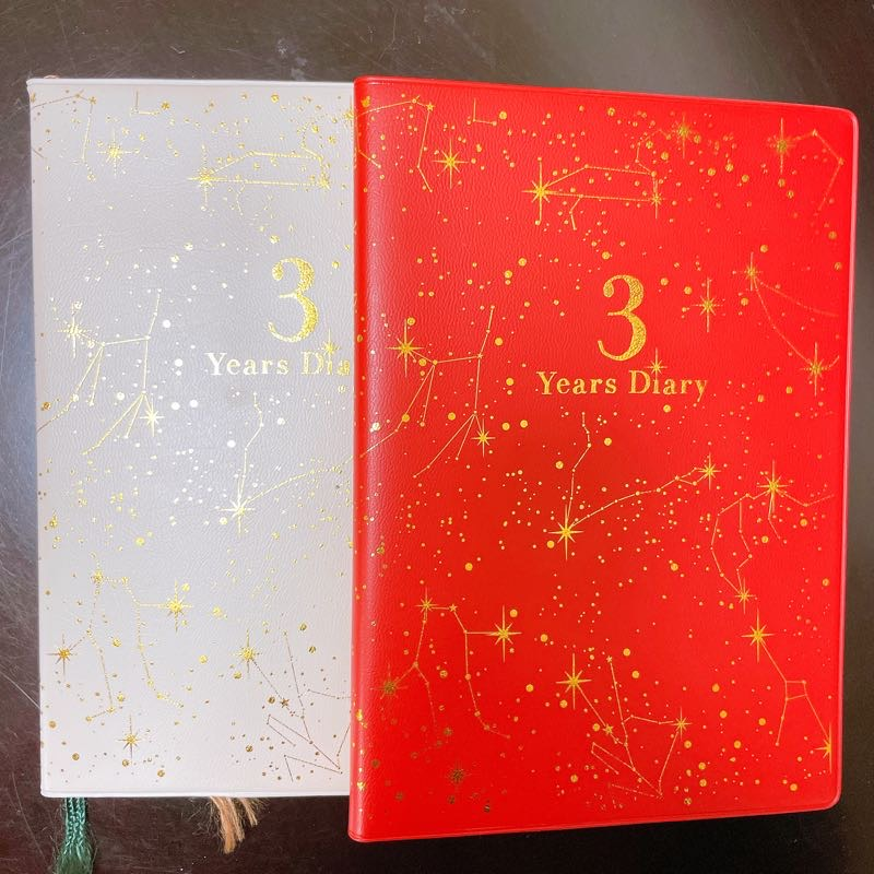 キラキラとしたラメのついた手帳が2冊。左側は白色、右側は赤色。