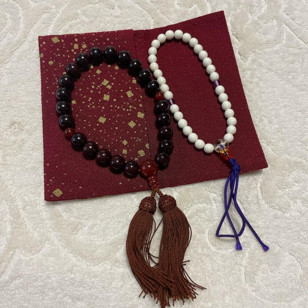 赤い布製の袋の上に大きめの黒の数珠と白い小さめの数珠が並んでいる写真