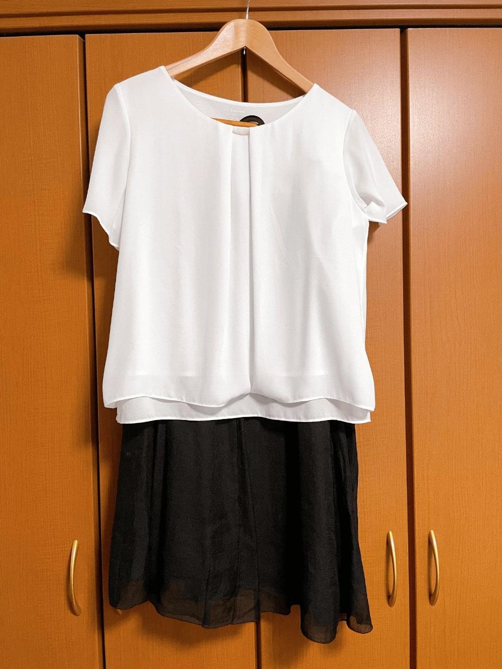 クローゼットに服がかかっている。白の半袖のカットソーと黒の麻のスカート