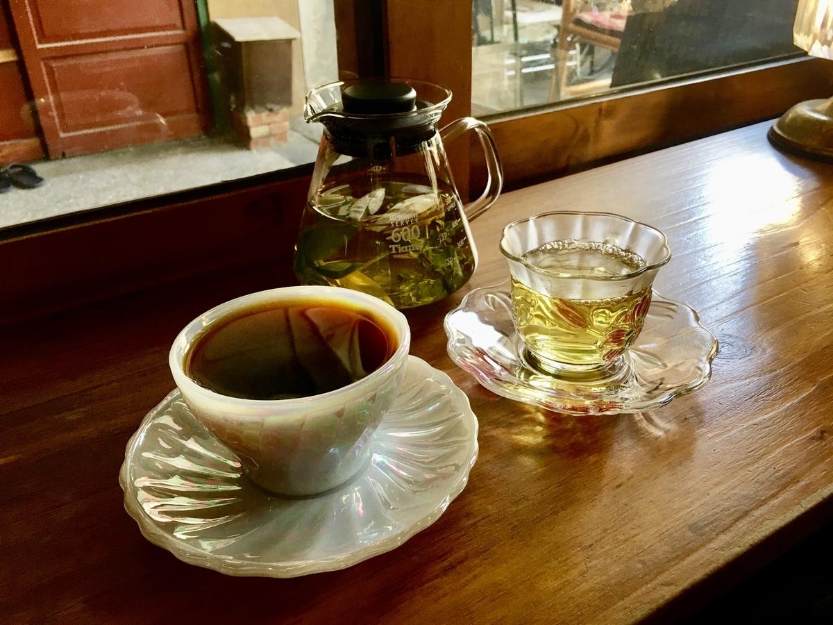 カップに入ったコーヒーと、ガラス製のカップに入ったお茶
