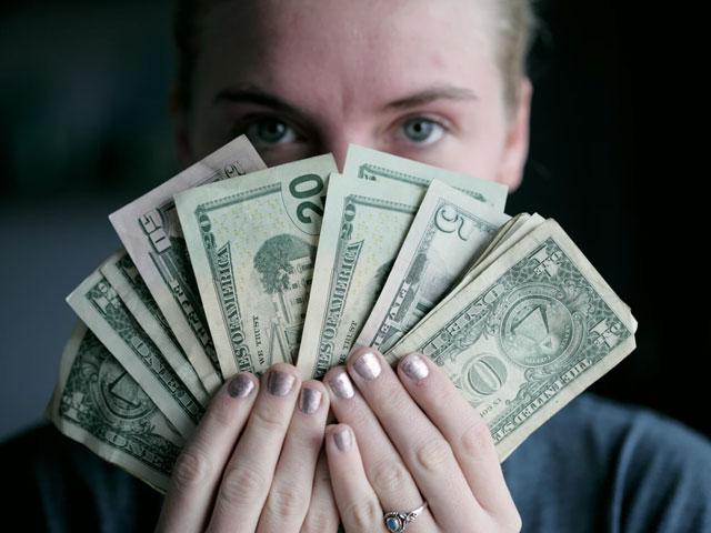 お札を手に持つ女性
