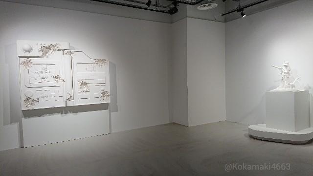左手にポケモン図鑑、右手にレッドとピカチュウ(ホワイト)の像がある写真
