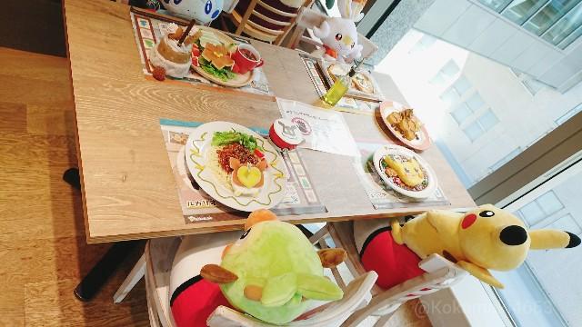椅子に座るメッソン・ヒバニー・サルノリ・ピカチュウのぬいぐるみと食品サンプルの写真