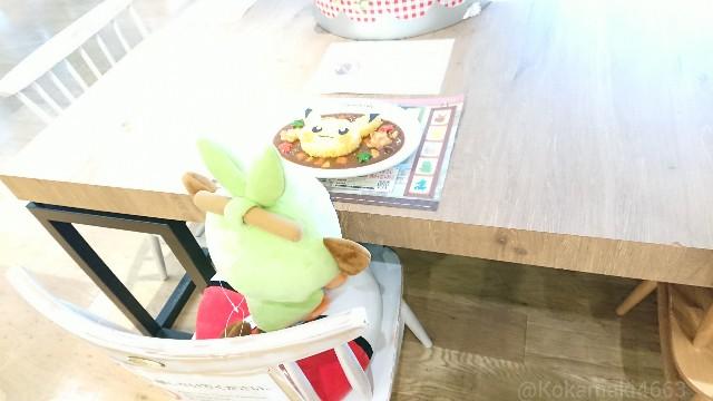 席に座ったサルノリと食品サンプルの写真