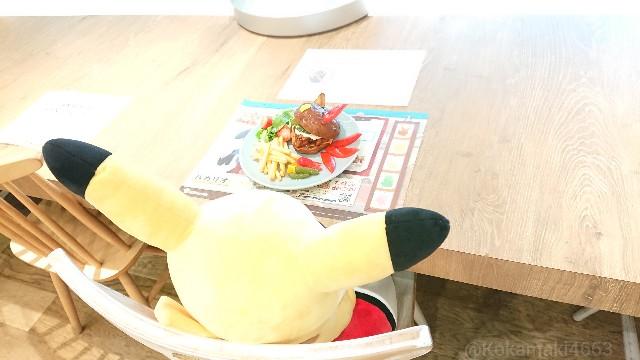 席に座ったピカチュウのぬいぐるみと食品サンプルの写真