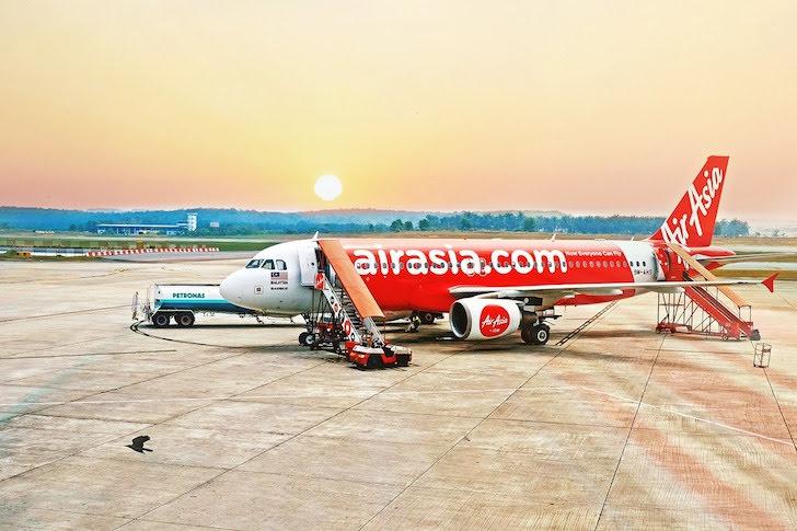 夕暮れの空港とエアアジアの旅客機