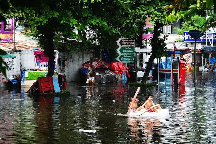 タイの洪水と手作りの小舟に乗る少年たち