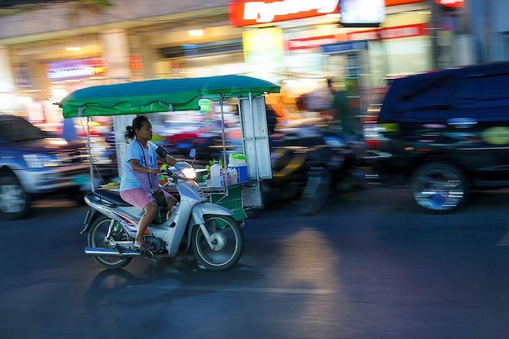 移動式屋台を運転して移動する女性