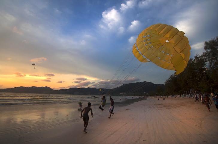 タイの砂浜でのパラセーリングをする男性たち