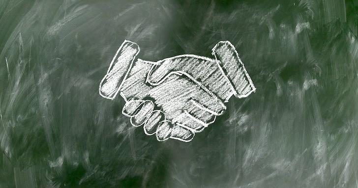 黒板にチョークで描かれた握手の絵
