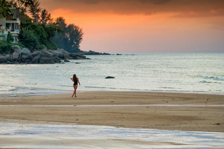 夕暮れの砂浜を歩く女性