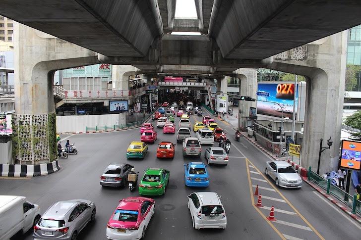 バンコクの高架鉄道の下を走るタクシー