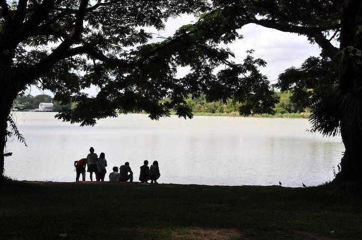 池のほとりでたたずむ家族連れ