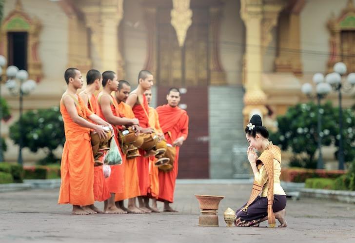 僧侶にひざまずくタイ人女性