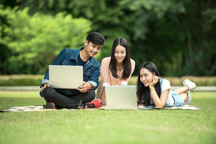 公園でノート型パソコンをのぞくタイ人の学生たち