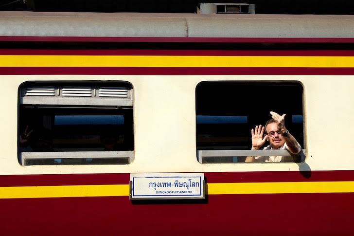 タイの列車から手を振る男性